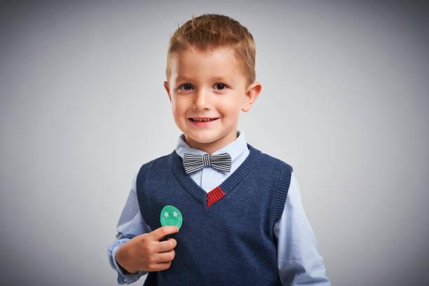 バッジで白いポーズをとる4歳の少年の肖像画 ストックフォト