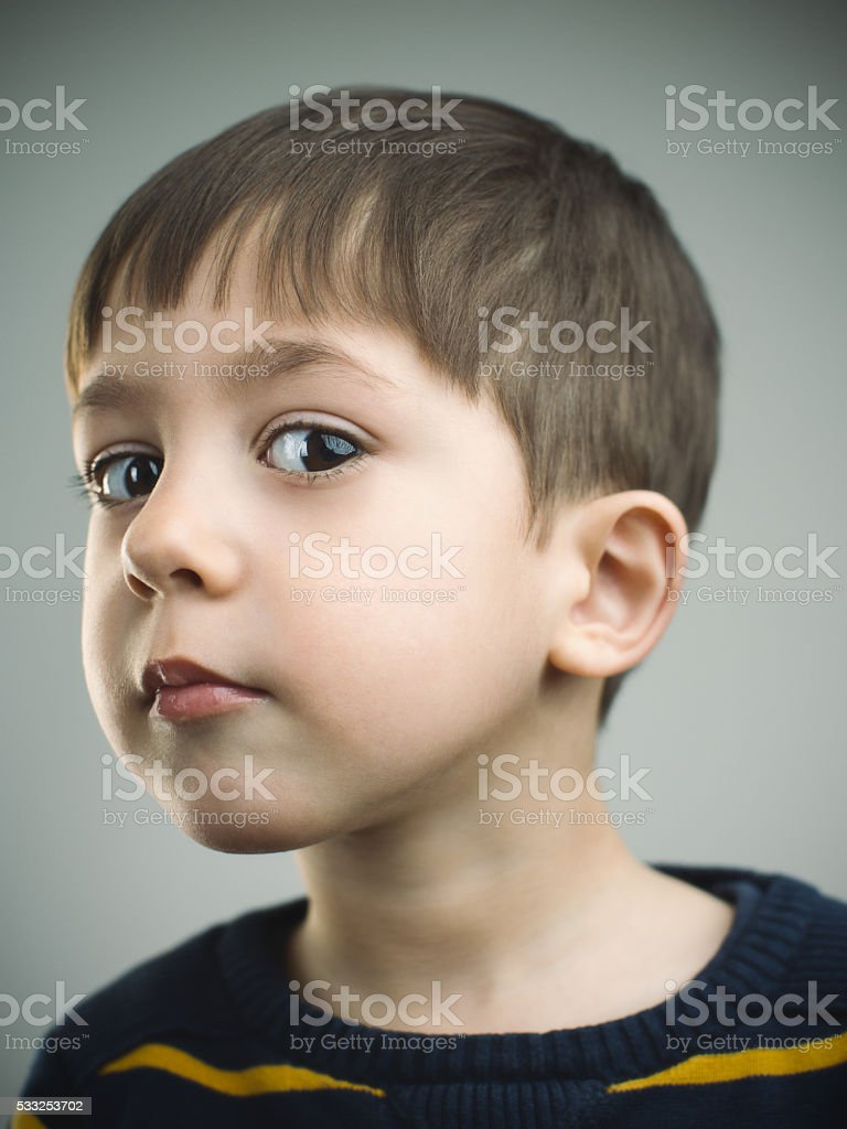 Portrait of a 4 years old boy with suspicious expression stock photo