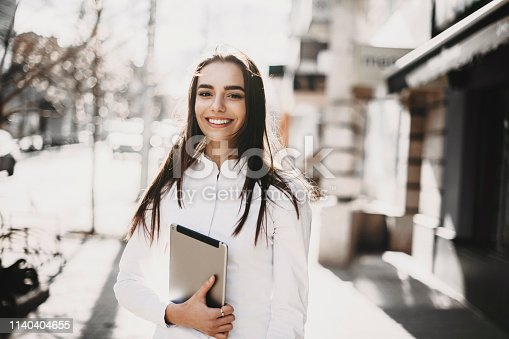istock Portrait of a amazing female freelancer holding a tablet and looking at camera smiling outside on the street. 1140404655