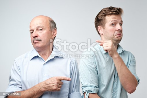 Portrait of two caucasian men pointing finger on each other. It was not me, he did it concept.