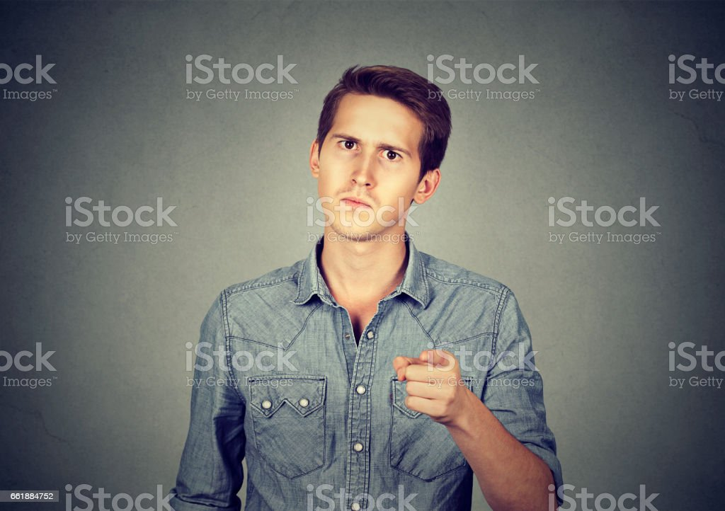 Portrait of a angry young man pointing finger at you camera stock photo