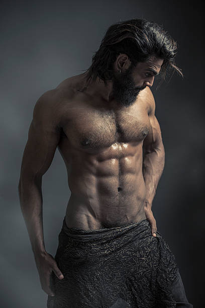Portrait of a athleltic muscular bearded man Portrait of a athleltic muscular bearded man posing on a grey background shirtless male models stock pictures, royalty-free photos & images
