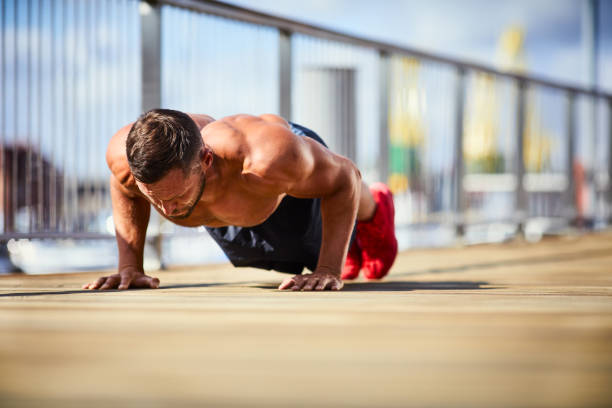 Portrait of a athletic man doing push-ups outside stock photo