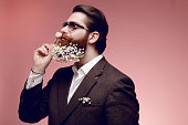 istock Portrait of a attractive brutal bearded man in sunglasses with flowers in beard, isolated on a dark pink background. 1148182242