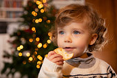 Beautiful baby girl eating cookies while decorating Christmas tree in family living room