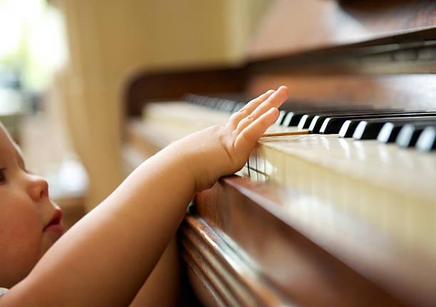 porträt von baby spielt klavier - lautbildungsspiele stock-fotos und bilder