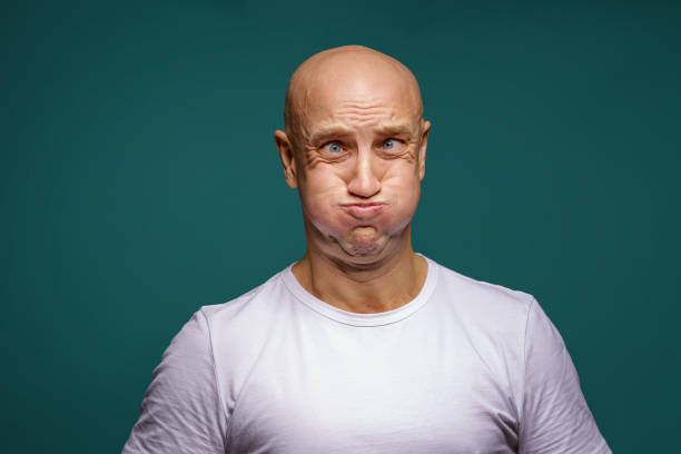 portrait of a bald man puffed out his cheeks on a blue background stock photo