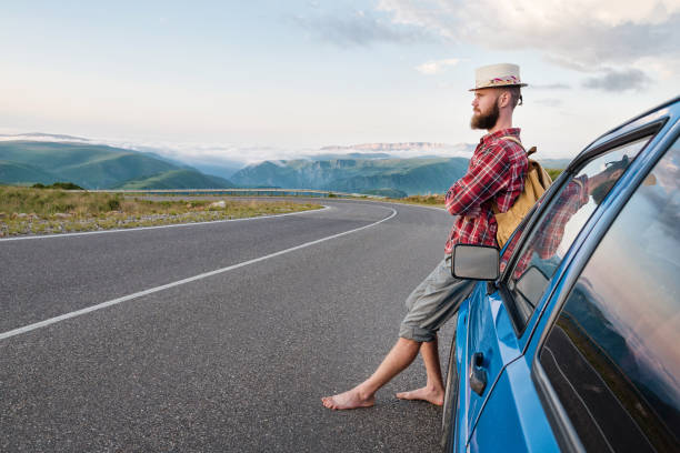 Portrait of a bearded happy traveler hipster with a backpack in a plaid shirt and a hat next to an unknown car stands on the road at sunset in the mountains. stock photo