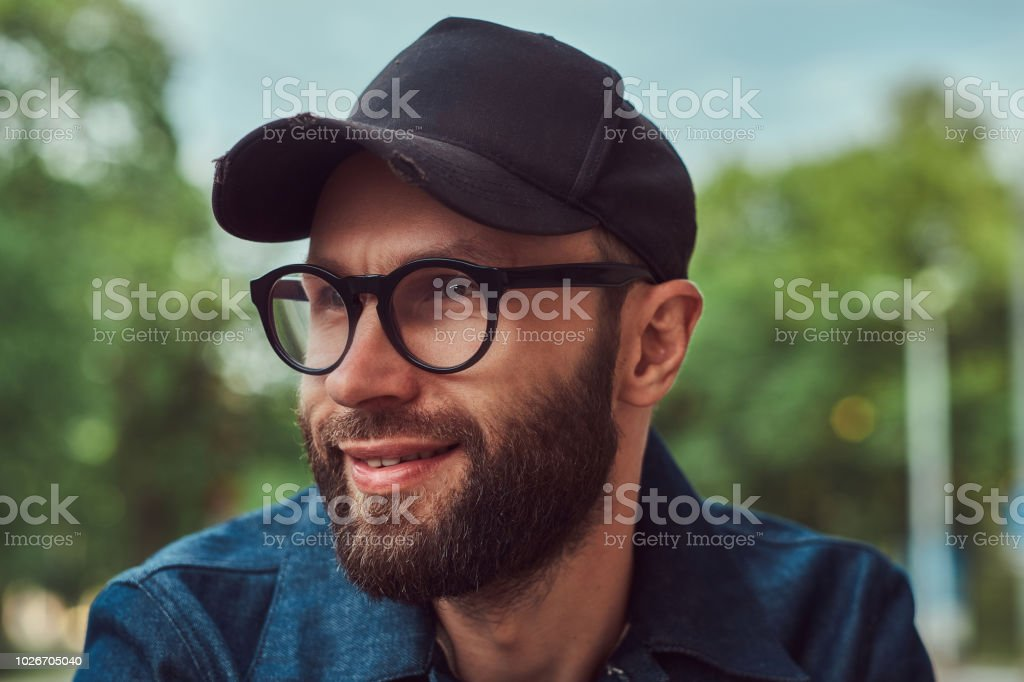 4bd86bb0ffc3 Portrait of a bearded hipster in glasses and cap outdoors. royalty-free  stock photo