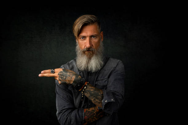 portrait of a bearded hipster, who is pointing with his fingers to something, isolated on a black background - rock musician stock pictures, royalty-free photos & images