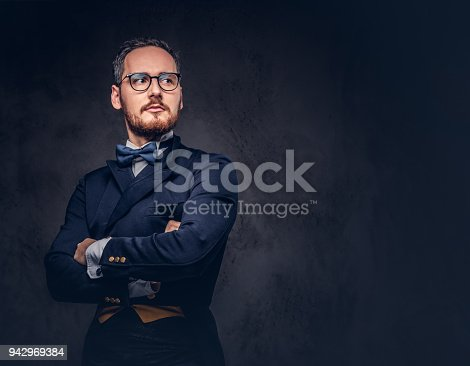 istock Portrait of a bearded male in glasses and antique suit on a dark 942969384