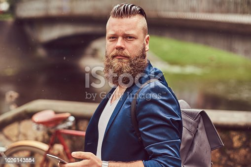 istock Portrait of a bearded male with a haircut dressed in casual clothes with a backpack, standing in a park, using a smartphone. 1026143884
