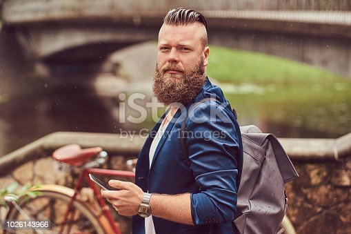 istock Portrait of a bearded male with a haircut dressed in casual clothes with a backpack, standing in a park, using a smartphone. 1026143966