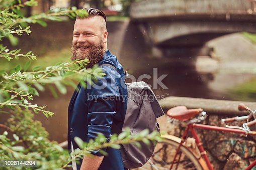 istock Portrait of a bearded male with a haircut dressed in casual clothes with a backpack, standing in a park. 1026144294