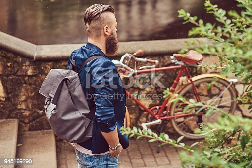 istock Portrait of a bearded male with a haircut dressed in casual clothes with a backpack, standing in a park. 945169290