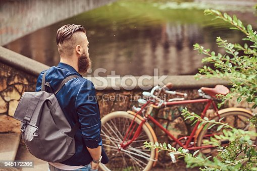 istock Portrait of a bearded male with a haircut dressed in casual clothes with a backpack, standing in a park. 945172266