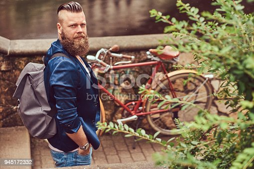 istock Portrait of a bearded male with a haircut dressed in casual clothes with a backpack, standing in a park. 945172332