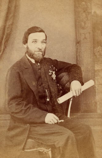 Victorian Man looking remarkably like Abraham Lincoln. Scanned from a pre-1900 family photo album. Aged paper texture visible in parts of the image.