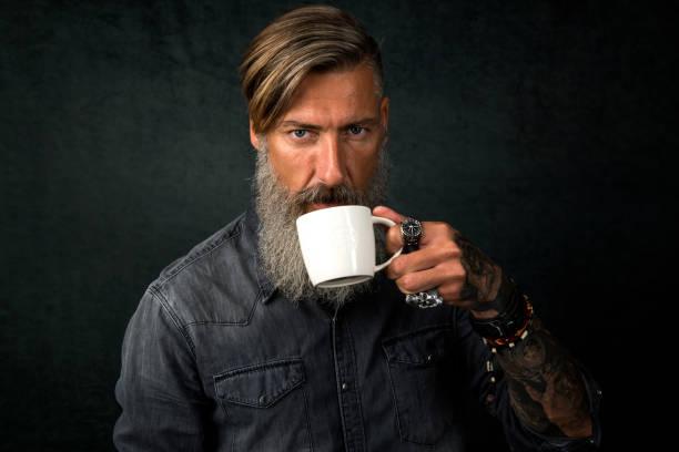 porträt eines bärtigen mannes mit einer tasse kaffee auf schwarzem hintergrund isoliert - porzellan schmuck stock-fotos und bilder