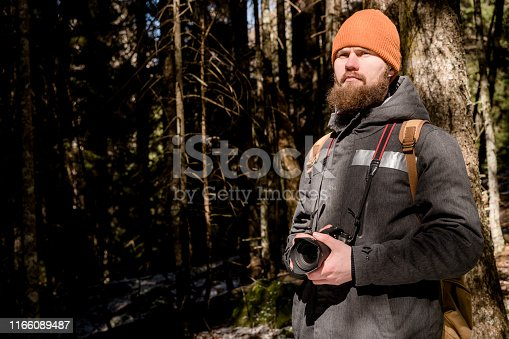 Portrait of a bearded photographer with a reflex camera in his hands in the winter coniferous forest. Photo travel concept.