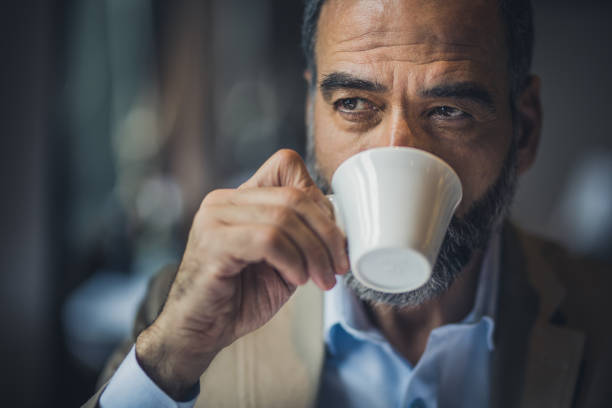 Portrait of a bearded senior man drinking coffee in a cafe. Thoughtful mature man drinking coffee in a cafe and looking away. only senior men stock pictures, royalty-free photos & images