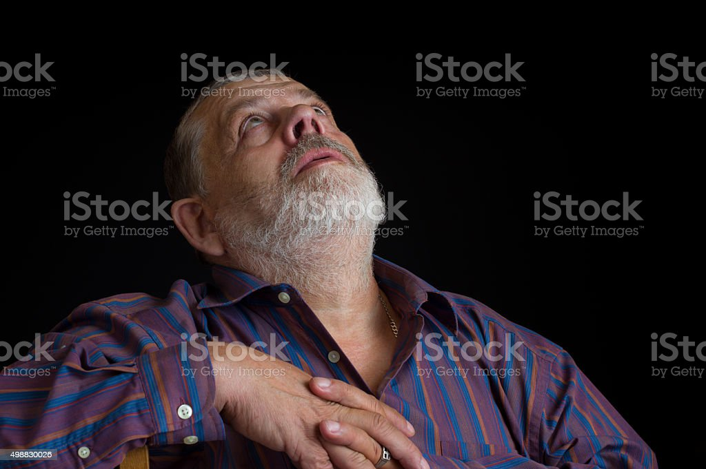 Portrait of a bearded senior man looking up stock photo