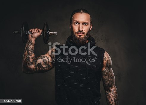 istock Portrait of a bearded tattooed athlete in a black hoodie posing with a dumbbell in hand. 1066290708