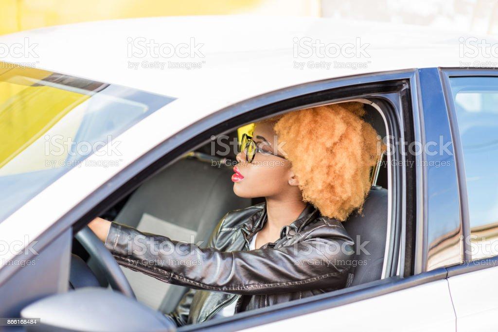 Retrato de una bella mujer africana en el coche - Foto de stock de 20 a 29 años libre de derechos