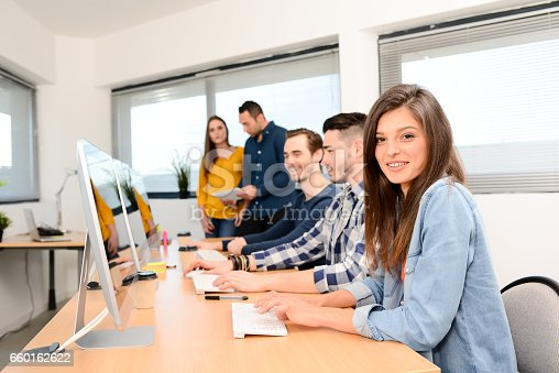 istock portrait of a beautiful and cheerful young woman in high school classroom working in computer on row with teacher and classmates in background 660162622