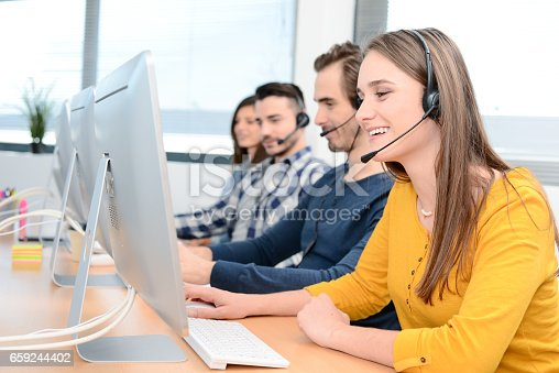 istock portrait of a beautiful and cheerful young woman telephone operator with headset working on desktop computer in row in a customer service call support helpline business center with teamworker in background 659244402