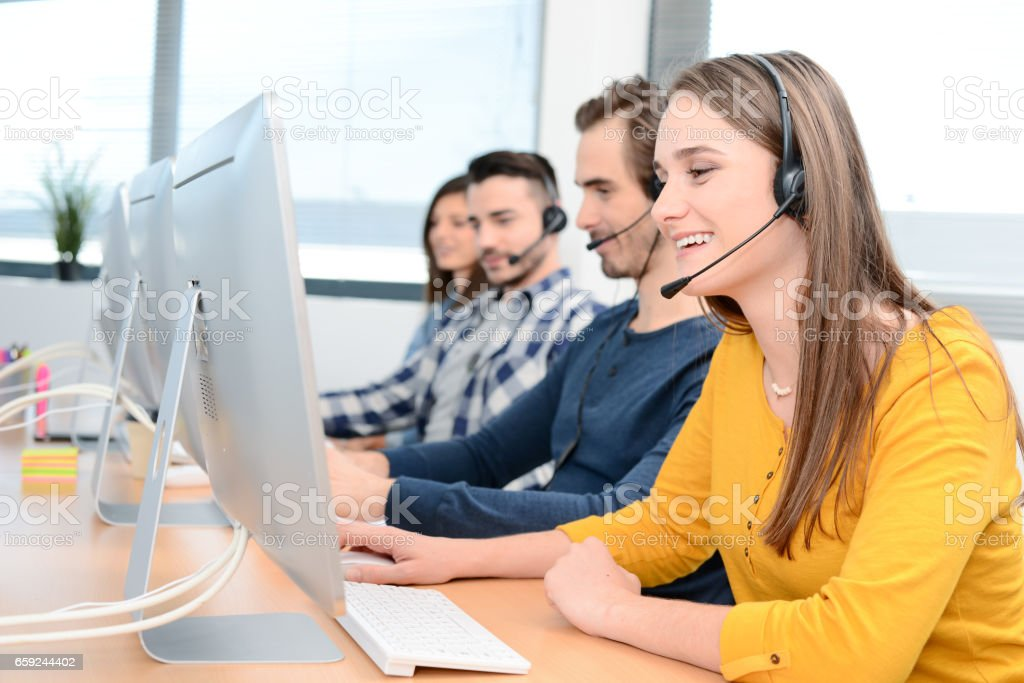portrait of a beautiful and cheerful young woman telephone operator with headset working on desktop computer in row in a customer service call support helpline business center with teamworker in background stock photo