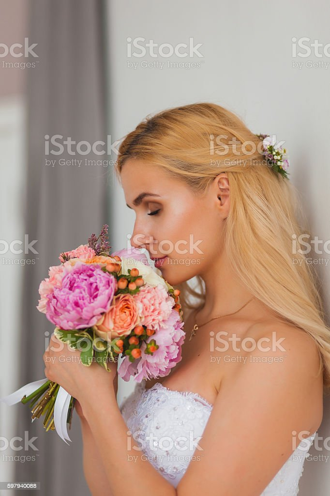 Portrait of a beautiful blonde bride with bouquet in an foto royalty-free