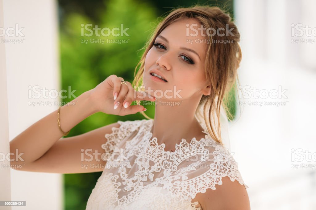 Portrait of a beautiful bride with a bewitching look. A model with white short hair enjoys a light wind in the park and walks. A girl with a beautiful make-up looks at the camera with a slightly stare zbiór zdjęć royalty-free