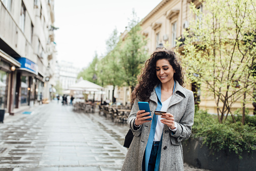 Portrait of a beautiful businesswoman enjoying in the city and shopping online.