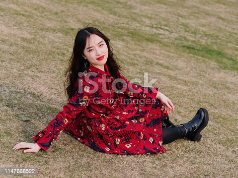 istock Portrait of a beautiful Chinese girl in red dress sitting on meadows and smiling at you. 1147666522
