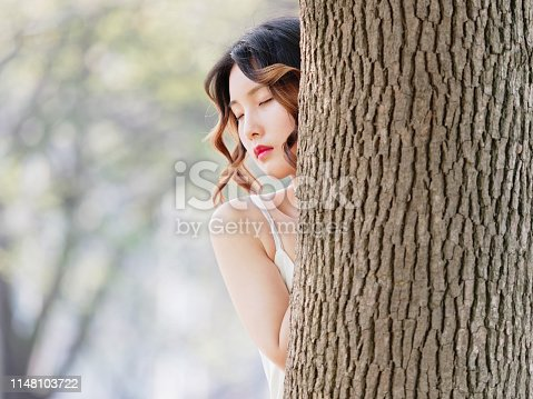 istock Portrait of a beautiful Chinese woman hide behind a tree and posing with eyes closed in a sunny day. Sexy girl in white dress and curly hair. 1148103722