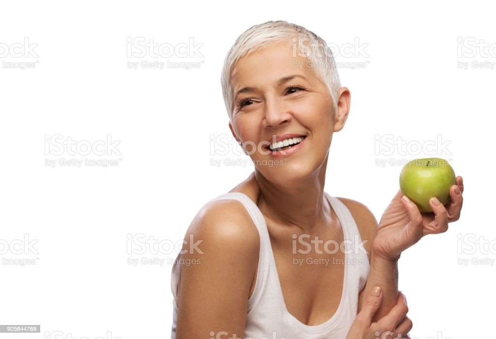Portrait of a beautiful elderly woman holding an apple, smiling, isolated on white background stock photo