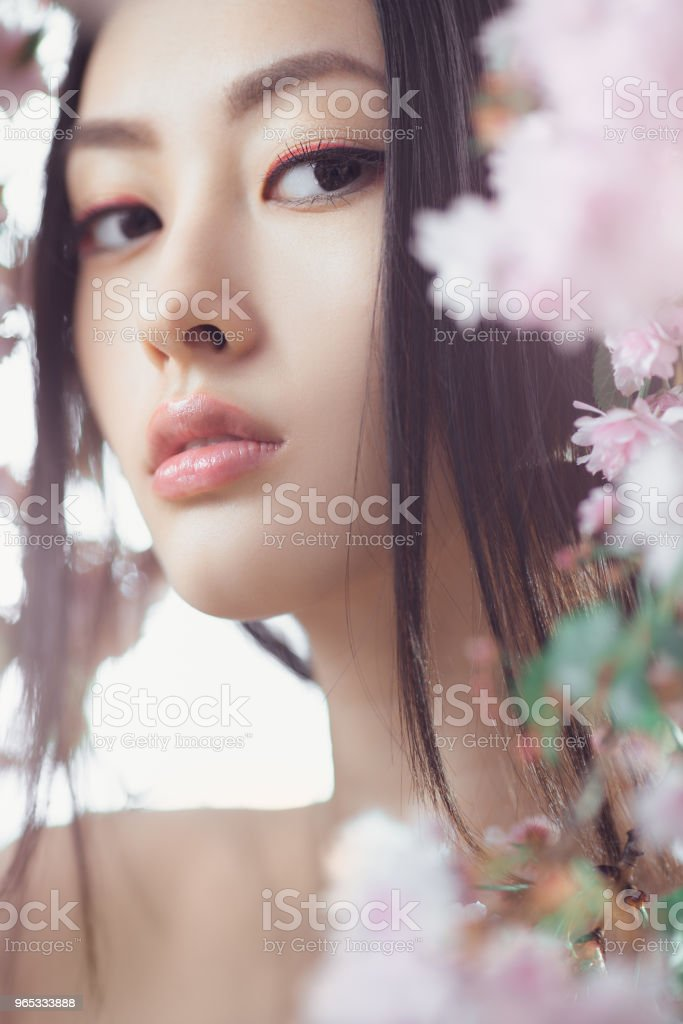 Portrait of a beautiful fantasy asian girl outdoors against natural spring flower background zbiór zdjęć royalty-free