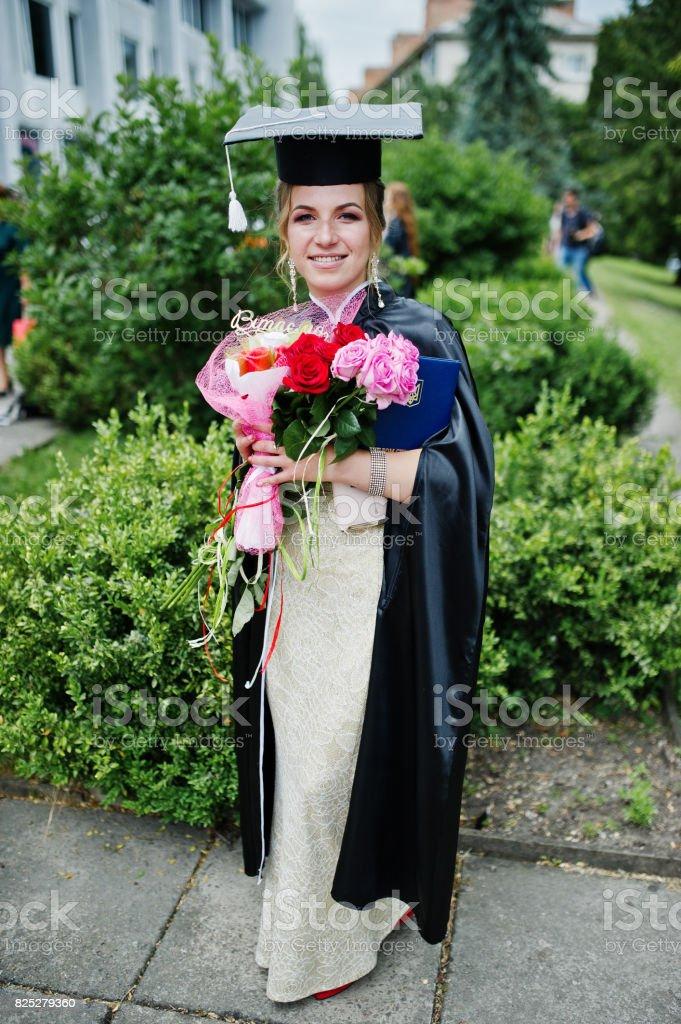 Retrato de un hermosa mujer graduado en vestido y graduación vestido con sombrero con flores. - foto de stock