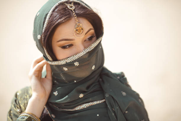 Portrait of a beautiful female model in traditional ethnic costume with heavy jewellery and makeup Beautiful Arabian woman portrait outdoors. Young Hindu woman. Portrait of beauty Indian model with bright make-up who hiding her face behind the veil standing over gold desert background. persian culture stock pictures, royalty-free photos & images