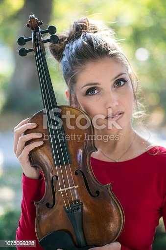 Portrait of a beautiful female violinist holding a violin outdoors. About 25 years old, Caucasian woman.