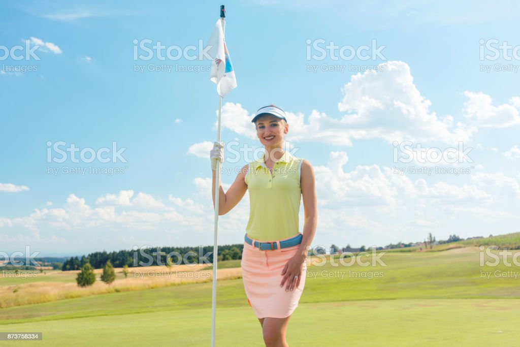 Portrait of a beautiful fit woman holding a flag stick outdoors on a professional golf course stock photo