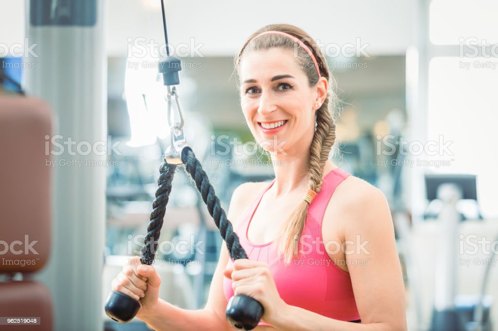 Portrait of a beautiful fit woman smiling while exercising for toned arms at the gym - Royalty-free Adult Stock Photo