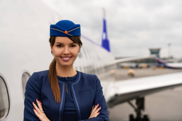 Portrait of a beautiful flight attendant Portrait of a beautiful flight attendant next to an airplane and looking at the camera smiling - travel concepts air stewardess stock pictures, royalty-free photos & images