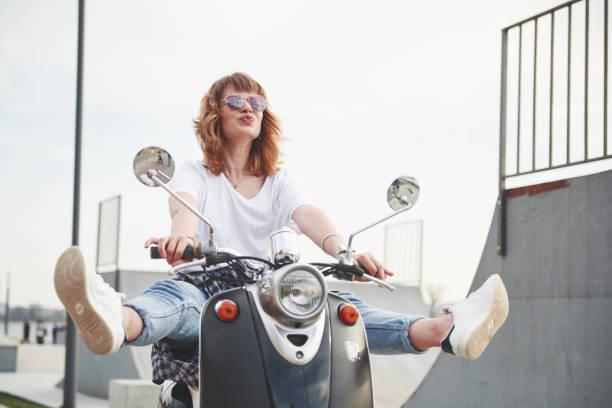 portrait d'un hipster de belle fille assise sur un scooter rétro noir, souriante posant et profiter du soleil de printemps au chaud. - moped photos et images de collection