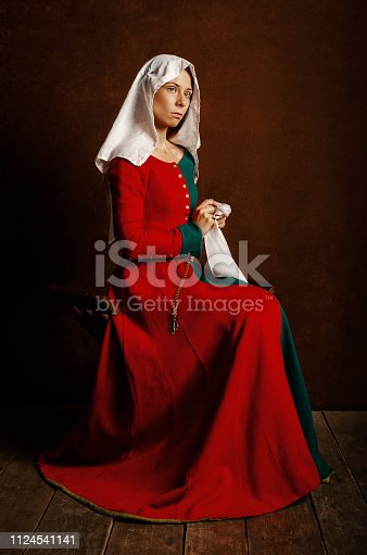 Portrait of a beautiful girl in a medieval dress in red and green on a brown background. Hobbies - the reconstruction of the medieval.