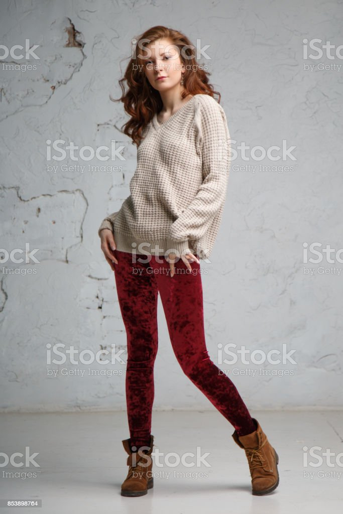 Portrait of a beautiful girl in a red sweater and jeans at full height on a gray background. stock photo