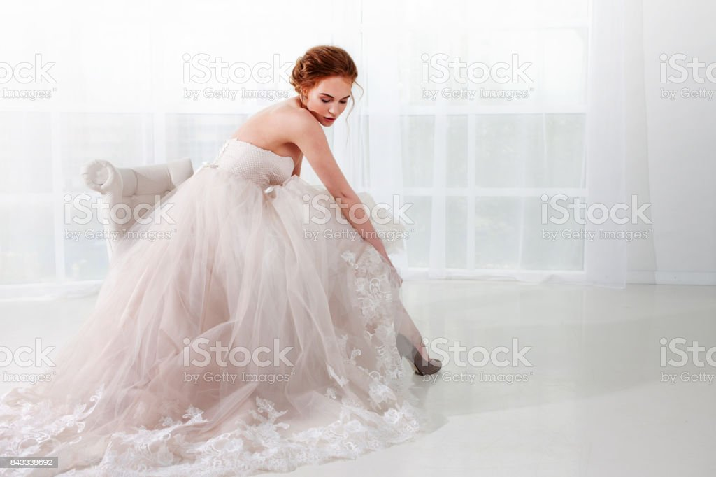 Portrait of a beautiful girl in a wedding dress. Bride in luxurious dress on a white background stock photo