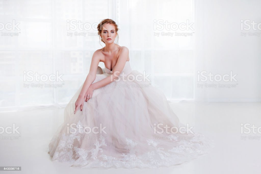 Portrait of a beautiful girl in a wedding dress. Bride in luxurious dress sitting on a chair stock photo