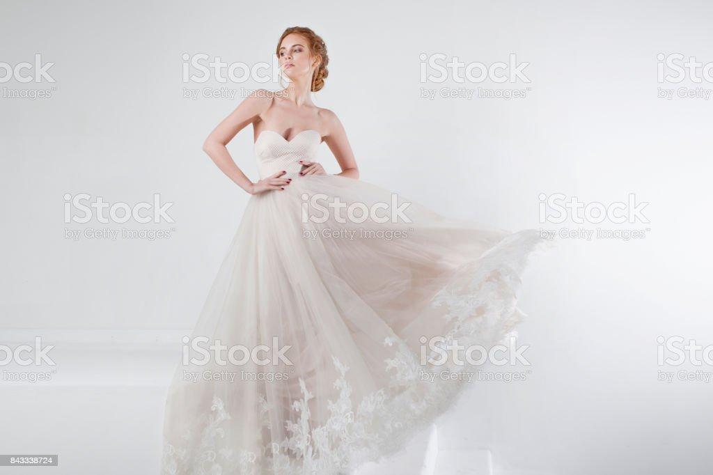 Retrato de una hermosa muchacha en un vestido de novia. Novia en vestido de lujo sobre un fondo blanco, las manos en la cintura - foto de stock